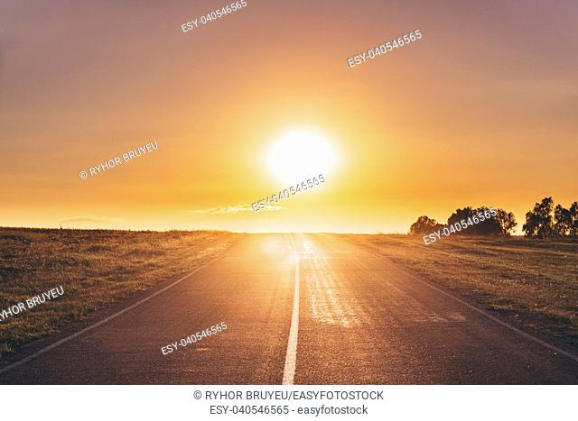 Sun Rising Over Asphalt Country Open Road In Sunny Morning Or Evening. Open Road In Europe In Summer Or Autumn Season At Sunny Sunset Or Sunrise Time