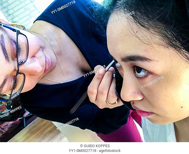 Tilburg, Netherlands. Young womna from the Dutch Antilles doing the make up of a young, Chinese woman, just before a photo shoot
