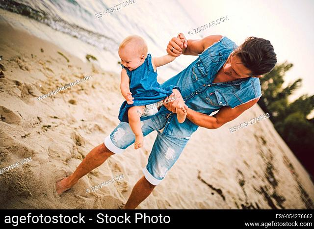 Theme Fatherhood and rest with a child at sea. Young handsome Caucasian father plays plays enjoys throwing up in arms his child up in summer daughter on the...