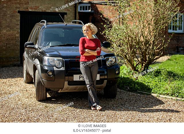 A mature woman standing in front of a car in the drive way of a house