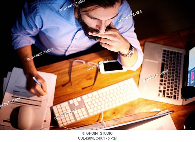 Overhead view of young businessman working at office desk at night