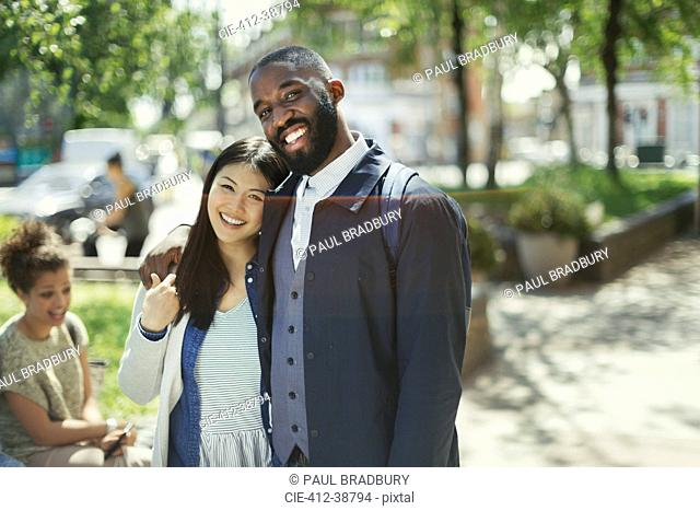 Portrait smiling, affectionate young couple hugging in sunny park