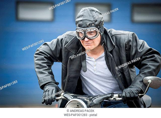 Man with leather jacket sitting on vintage moped