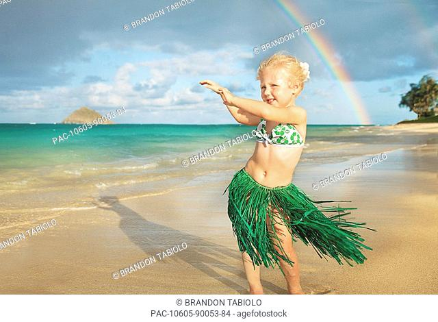 Hawaii, Oahu, Young girl in a hula skirt dancing on the beach, rainbow in background