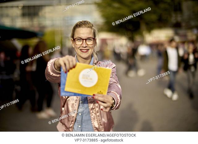 Woman with city tour guide maps between pedestrians in Berlin, Germany