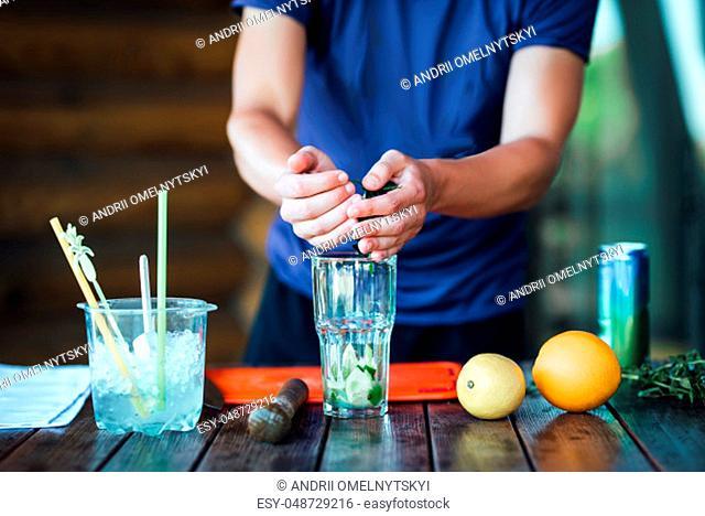 Barman prepares fruit alcohol cocktail based on lime, mint, orange, soda and alcohol