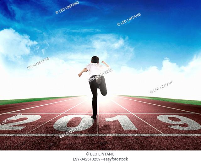 Rear view of asian businessman running on running track with 2019 number on start line. Happy New Year 2019