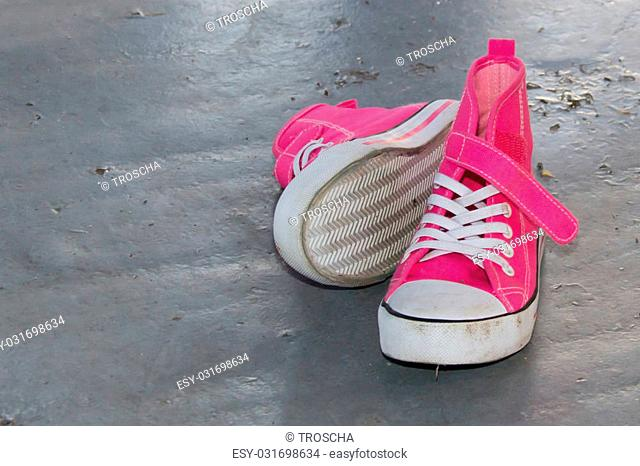 Hot pink baby's first shoes on the gray floor