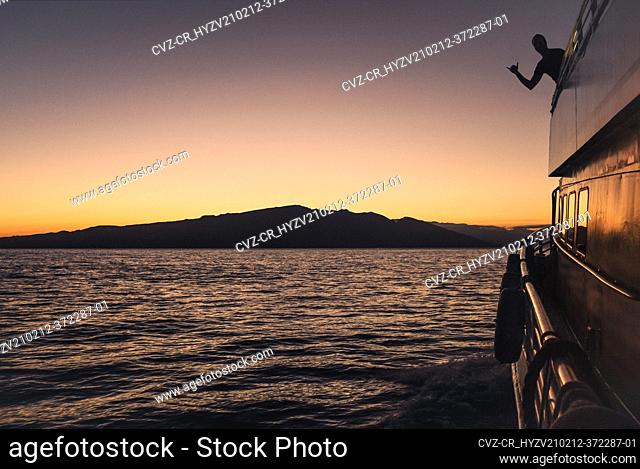 A man's silhouette shows shaka on sunset cruise with Maui in distance