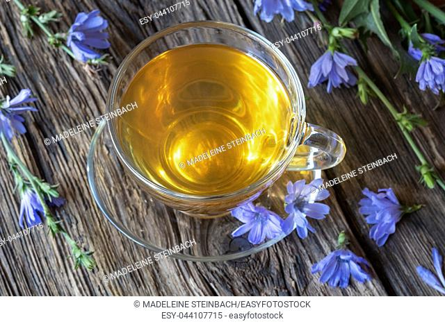 A cup of chicory tea and flowers on a rustic background
