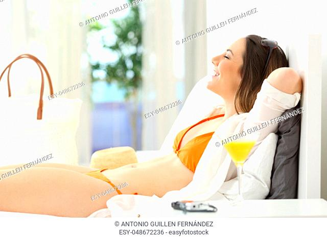 Side view portrait of a happy woman relaxing in an hotel room on summer vacations