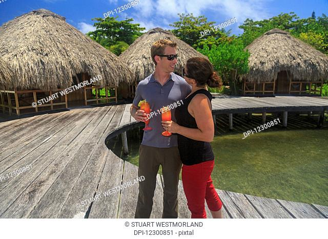 Couple on a wooden boardwalk with refreshing drinks at Saint Georges Caye Resort; Belize City, Belize