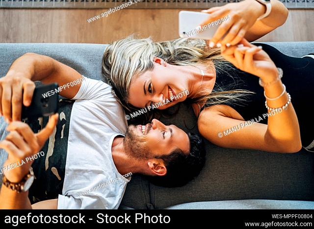 Happy couple lying on the couch taking selfies with smartphones while looking at each other