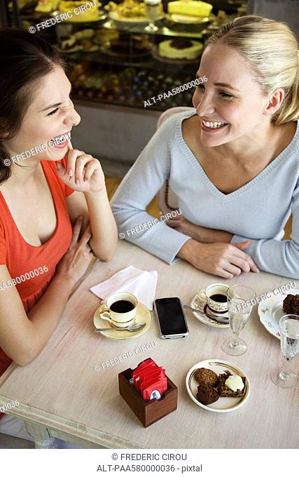 Female friends having coffee together at cafe