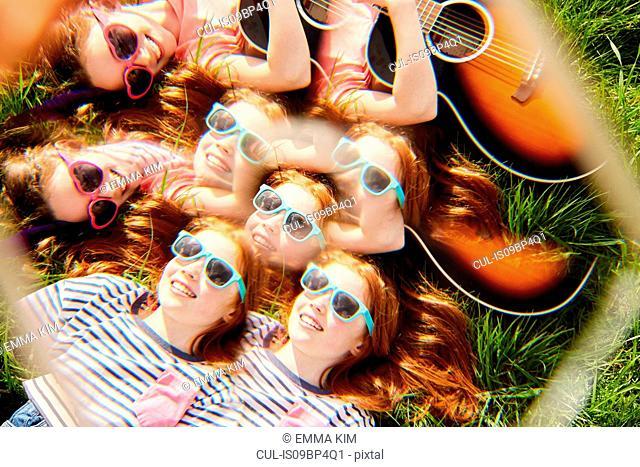 Girls playing guitar on grass