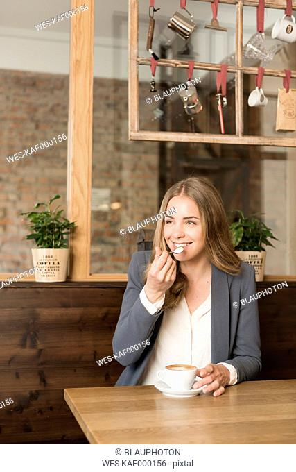 Portrait of smiling young woman tasting cappuccino in a coffee shop