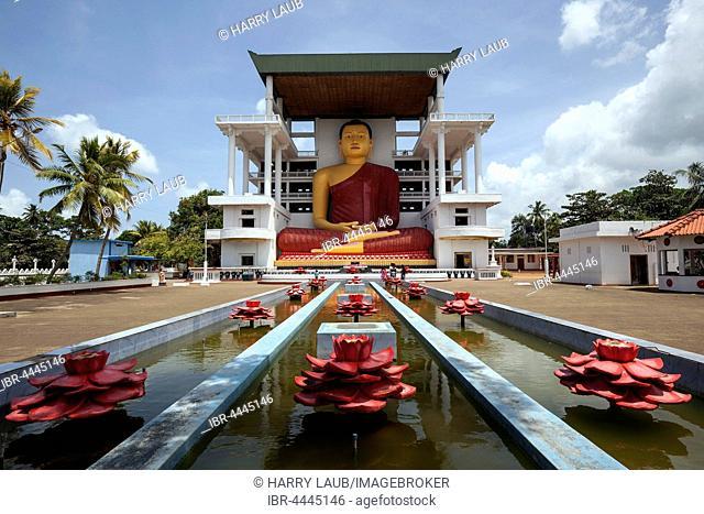 Giant Buddha statue, sitting Buddha fountain with artificial lotuses, Weherahena Temple, Matara, Southern Province, Sri Lanka