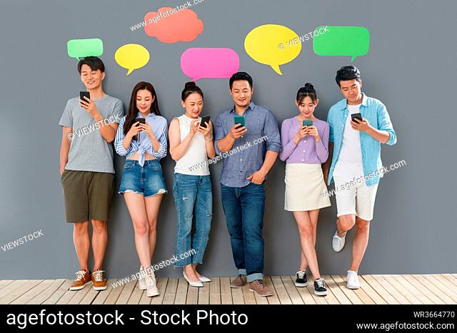 In the happy young people use mobile phone chat software to communicate
