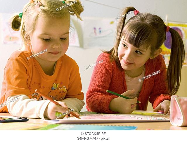 Two girls drawing with color pencils