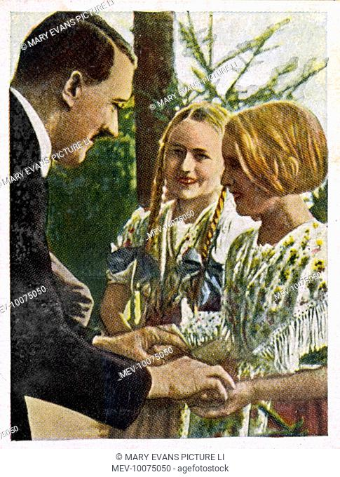 ADOLF HITLER Relaxing with two young Bavarian girls, circa 1933