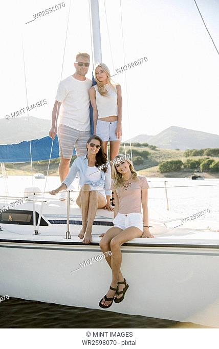 Man, woman and their two blond daughters on a sail boat