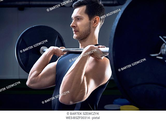 Man doing push press barbell exercise at gym