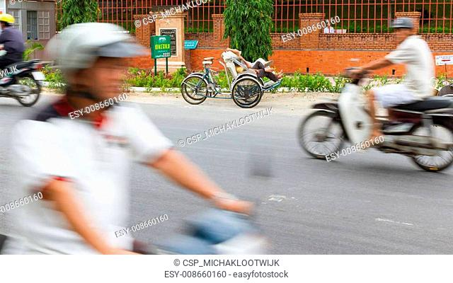 DA NANG, VIETNAM, 31 JULY 2012. Sleeping cyclo driver in it's own cyclo. Sightseeing by cyclo is an old tradition in Da Nang