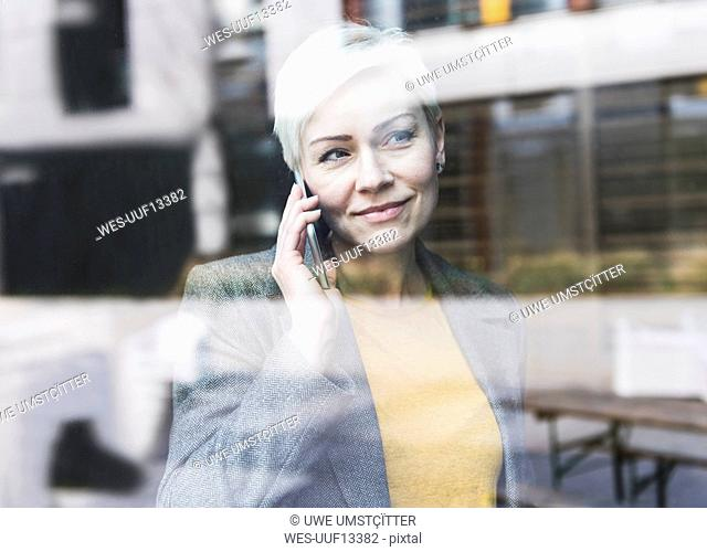 Portrait of confident businesswoman on cell phone behind windowpane