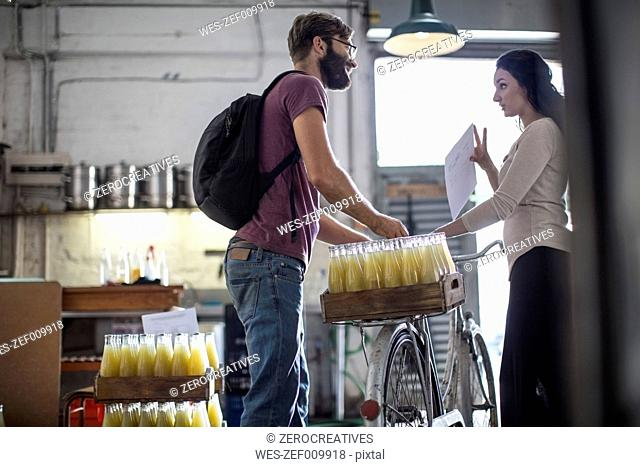 Delivery man with juice bottles on bicycle talking to woman in warehouse