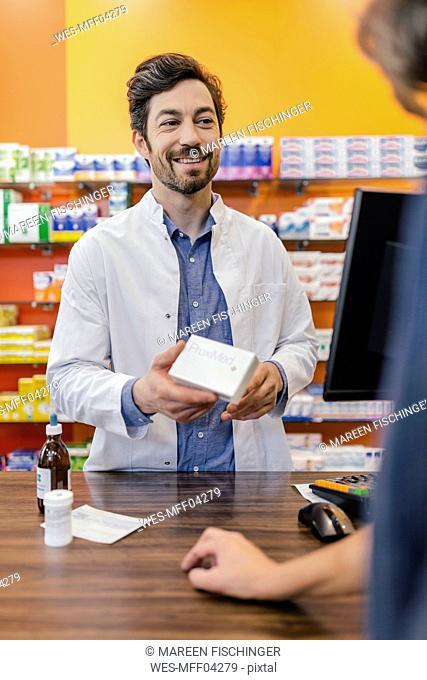 Pharmacist explaining medicine to customer in pharmacy