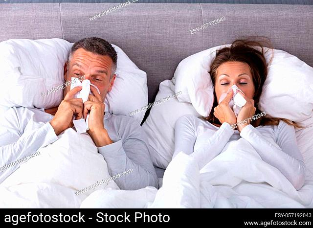 Close-up Of Mature Couple Lying On Bed Blowing Their Nose In Bedroom