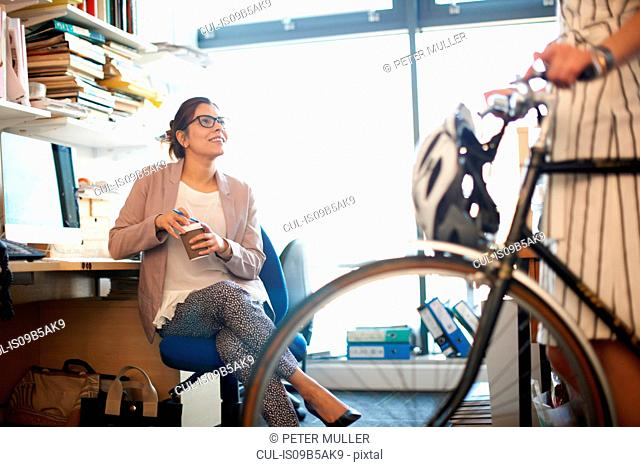 Woman in office with coffee chatting to colleague