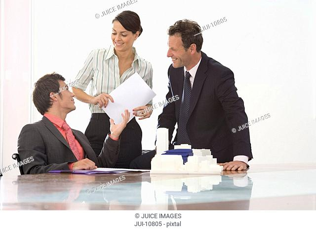 Businessman at meeting room table giving paperwork to colleague, smiling