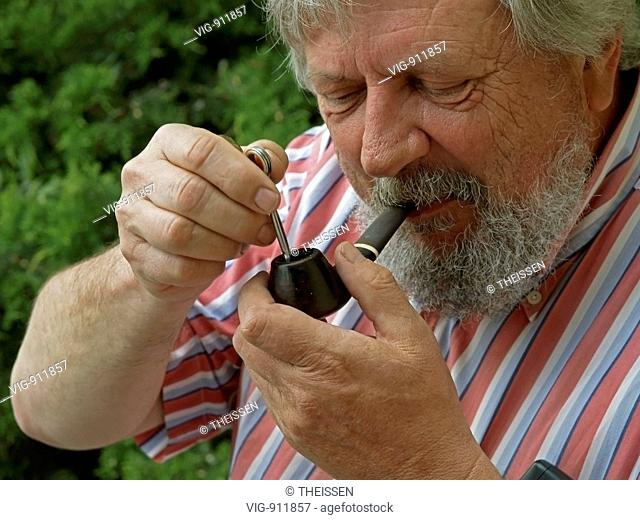 elder bearded man lighting his pipe with a cigarette lighter . - 27/04/2007