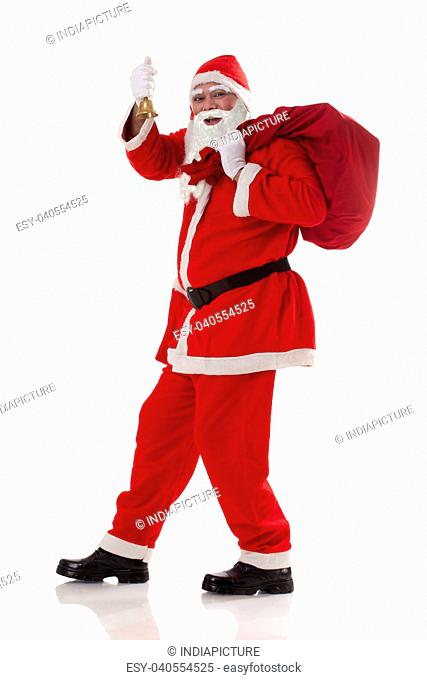 Full length of Santa Claus carrying sack of presents with bell