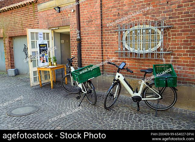 09 April 2020, Schleswig-Holstein, Lübeck: Electric bicycles are available for delivery drivers at the rear entrance of a delivery service