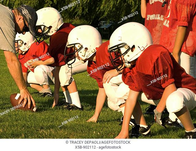7 and 8 year old American Football players at practice  Atom division  On the line in practice  horizontal