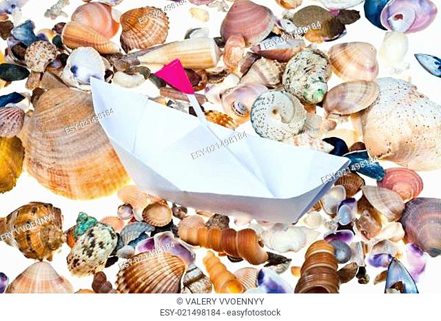 paper boat with flag on background from sea shells