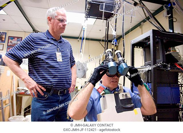 NASA astronaut Steve Bowen, STS-133 mission specialist, uses virtual reality hardware in the Space Vehicle Mock-up Facility at NASA's Johnson Space Center to...