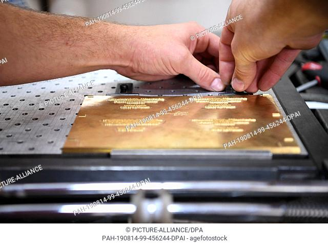 09 August 2019, Berlin: Lars-Peter Leu, manufacturer of business cards, sets up a brass plate for the platen printing press