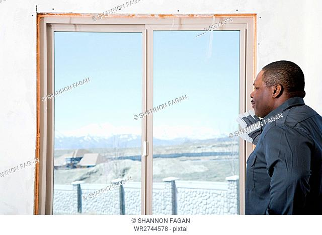 A builder looking out of a patio door