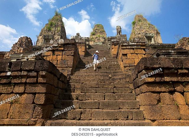 Woman descending steep steps at East Mebon Temple, built by Rajendravarman in the 10th Century; Cambodia