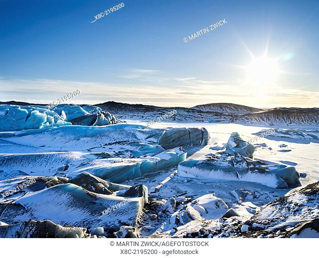 Svinafellsjoekull glacier in Vatnajoekull NP during Winter, view over the frozen glacial lake and the melting glacial front