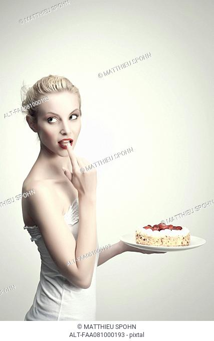 Young woman holding strawberry cake, licking cream off finger, portrait