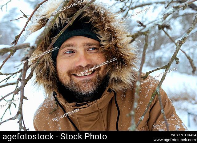 Portrait of smiling man wearing hooded jacket in winter