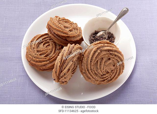 Piped biscuits with chocolate filling on a white plate