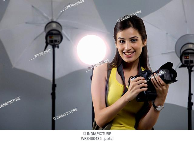 Portrait of beautiful young photographer holding camera in her studio