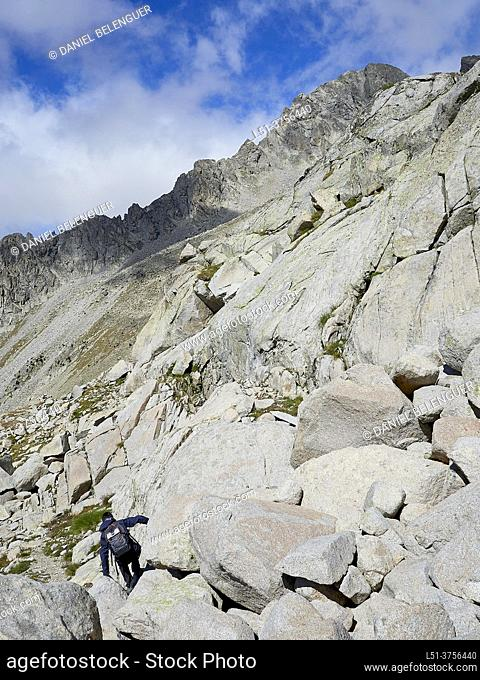 Woman hiking on a bed of rocks along the Cregueña Valley, Benasque, Aragón, Spain