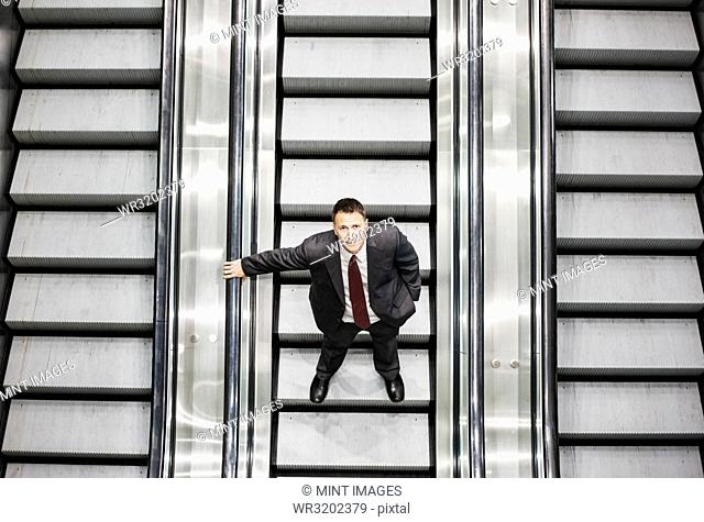 Looking down on a Caucasian businessman looking up while riding an escalator in a convention centre