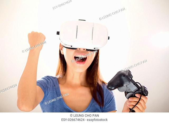 Excited Asian Woman play game with VR device